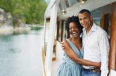 An older Black couple hangs off a boat