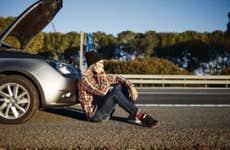 A man sits by his car that broke down.