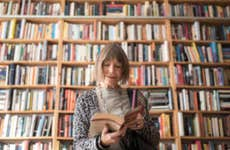 An old white woman flips through a book in front of a bookshelf