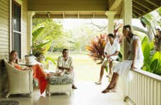A group of friends sit outside on their porch in Hawaii.