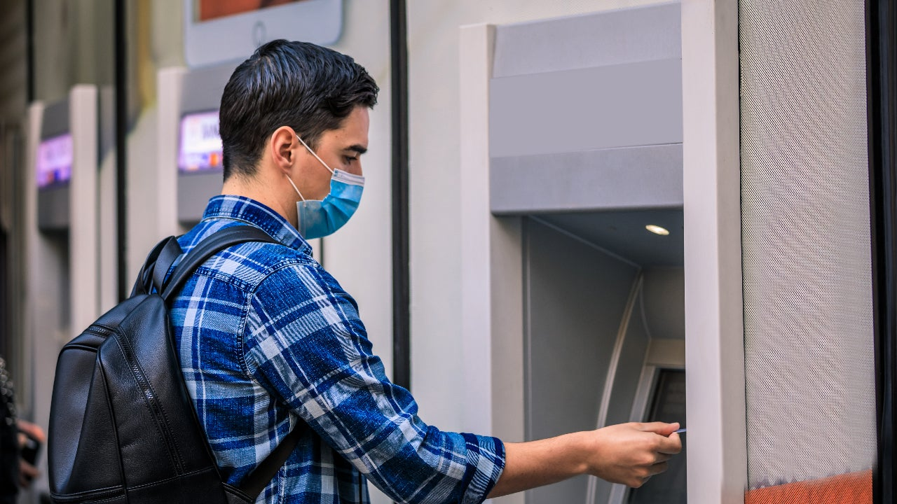 Man using ATM for cash withdrawal.