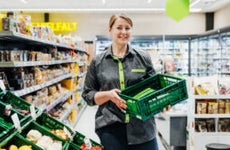 A female grocery employee holds a basket