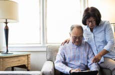 An older Asian couple sitting in their living room on a laptop, reviewing their finances.