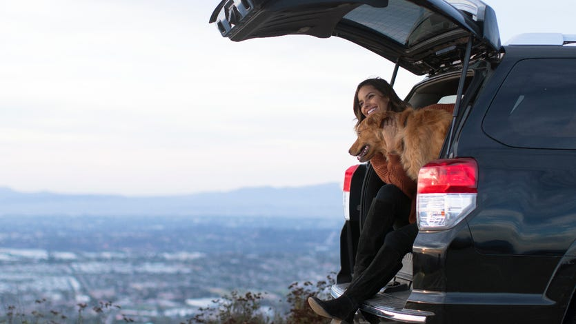 Young woman sitting in the back of her car with her golden retriever