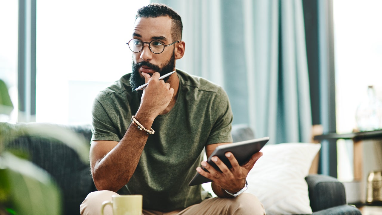 A man sits with a tablet looking pensive