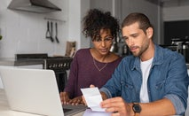 Young couple work on finances at kitchen table