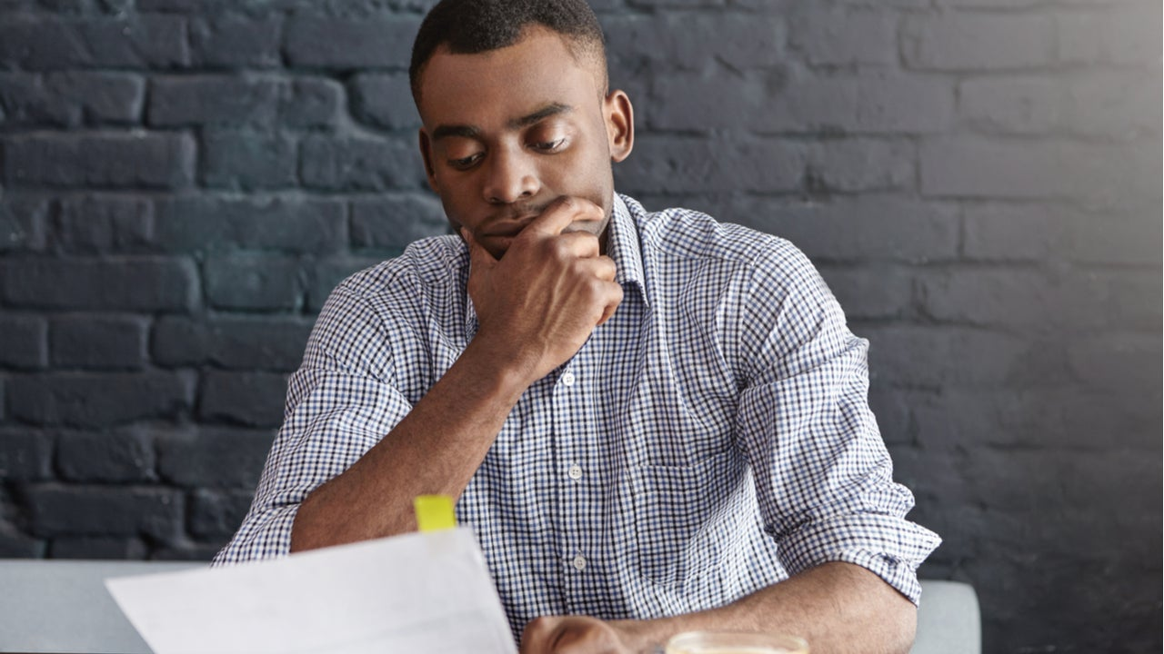 Young man with ponderous expression reviewing paperwork