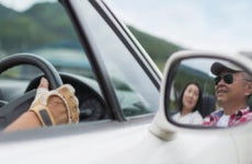 An older Asian couple enjoying a nice drive (you can see their smiling faces reflected in the sideview mirror)