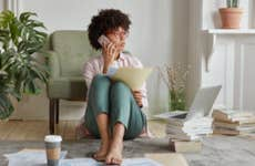 Young woman sitting on living room floor organizing finances on phone