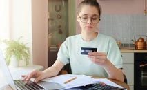 Young woman uses credit card to make online purchase