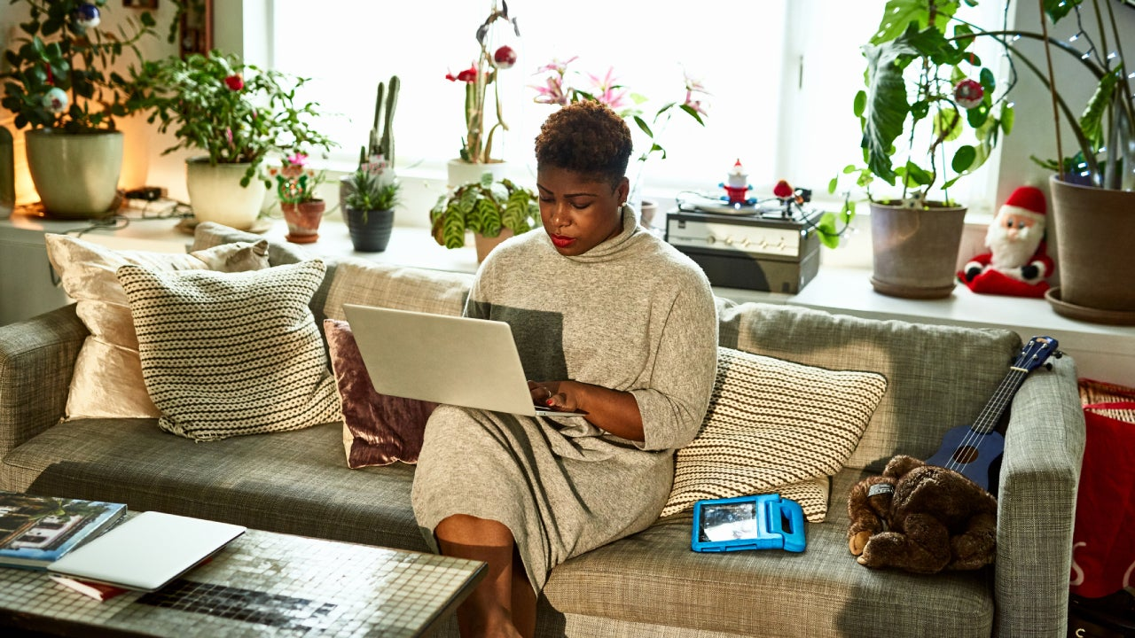A black lady sits in her living room working on her laptop.