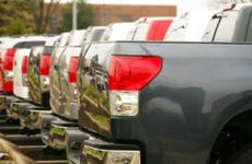 A row of trucks parked at a car dealership
