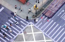 A picture from above of pedestrians crossing a busy street