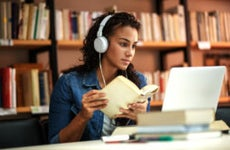 Young college student studying in library while wearing headphones