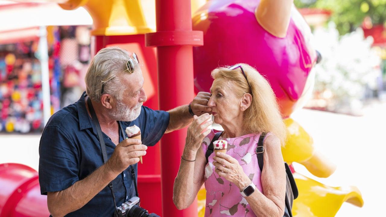 An older couple enjoys some ice cream at an amusement park.