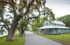 A home on the Florida coast with Spanish moss hanging off the tree branches.