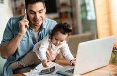 Father working from home while holding baby daughter