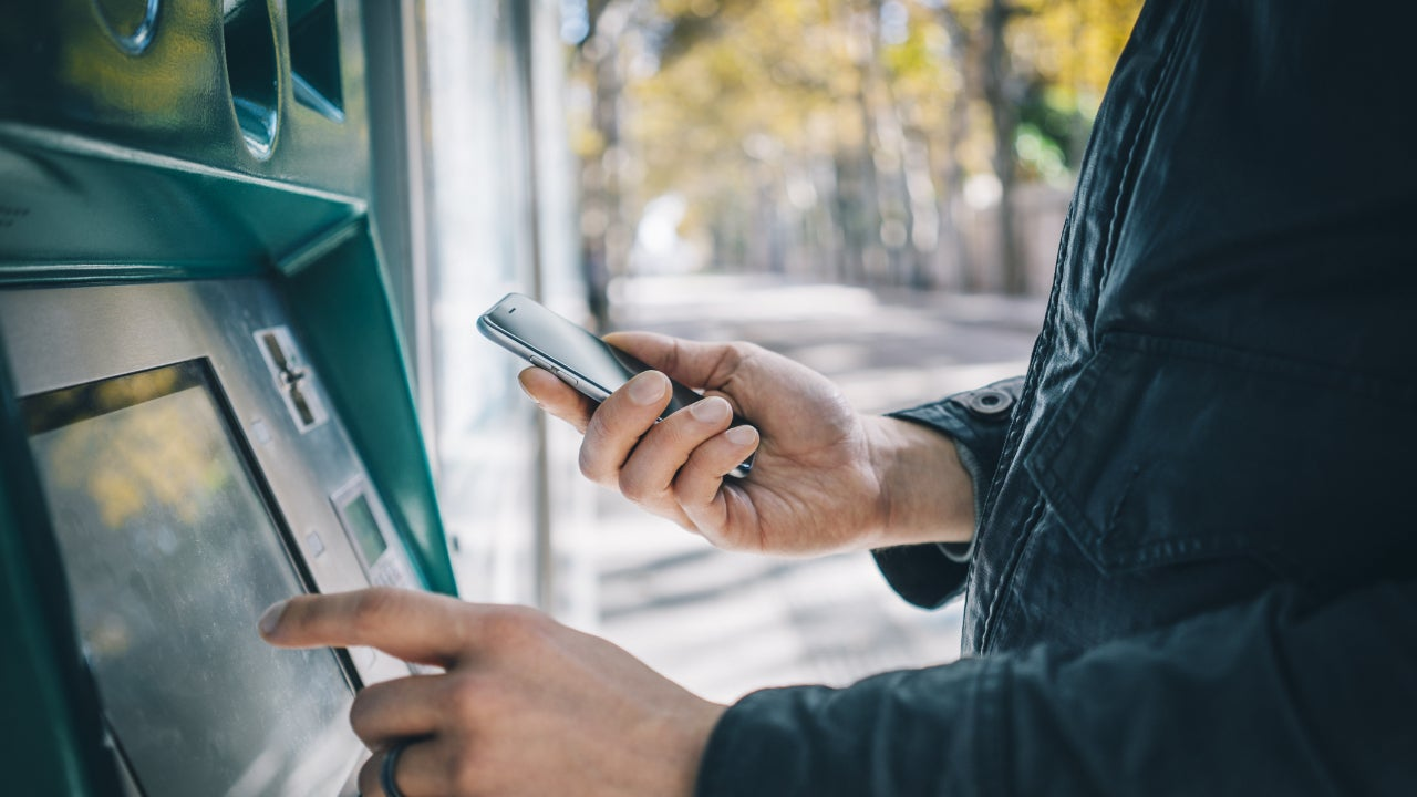 A man uses his phone at an ATM.