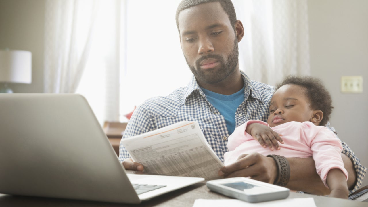 A single father sits with their child in one arm and a financial record in the other, reviewing finances.