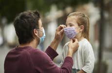 A father helps put a mask on his daughter to protect against COVID-19.