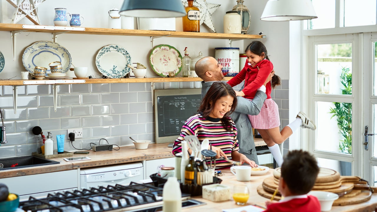 A father holds his daughter up in the air while mom is making lunches and smiling in the kitchen.