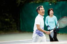 An older Asian man holds a tennis racket on a court and shouts in joy after scoring a point.