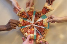 seven hands each take a slice of pizza from the same pie