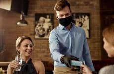 Happy waiter wearing face mask while his guests are making contactless payment in a cafe.