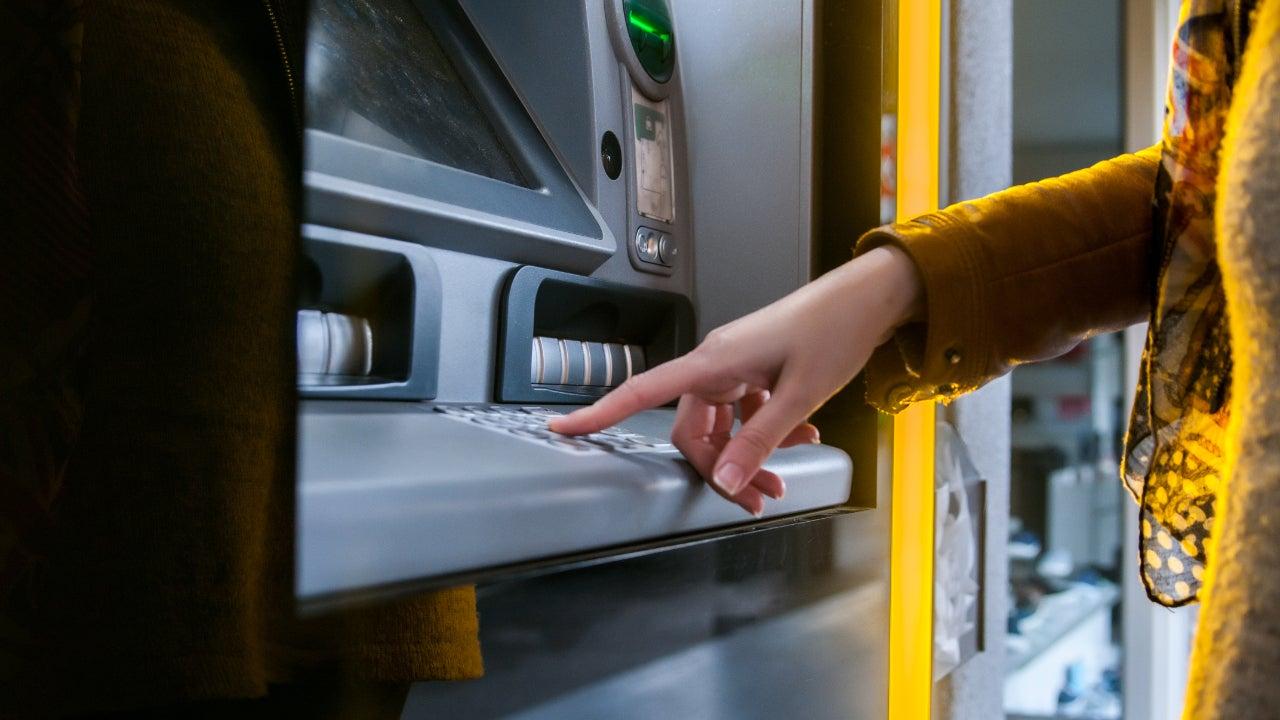 A woman visits an ATM.