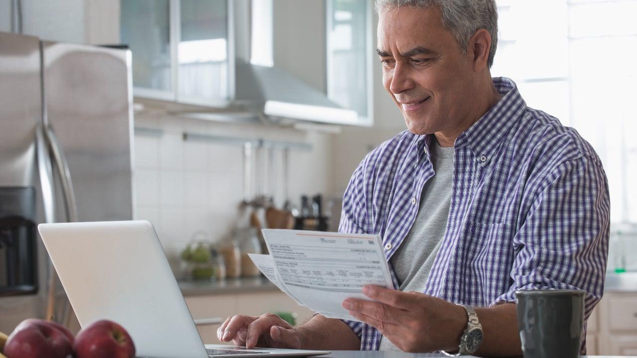 Man paying bills online in kitchen