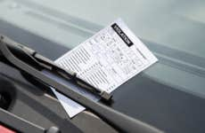 Shot of a parking ticket secured to a windshield by a wiper.