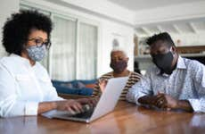 Some people wearing facemasks are on a laptop trying to figure out what to do with their life insurance policy.