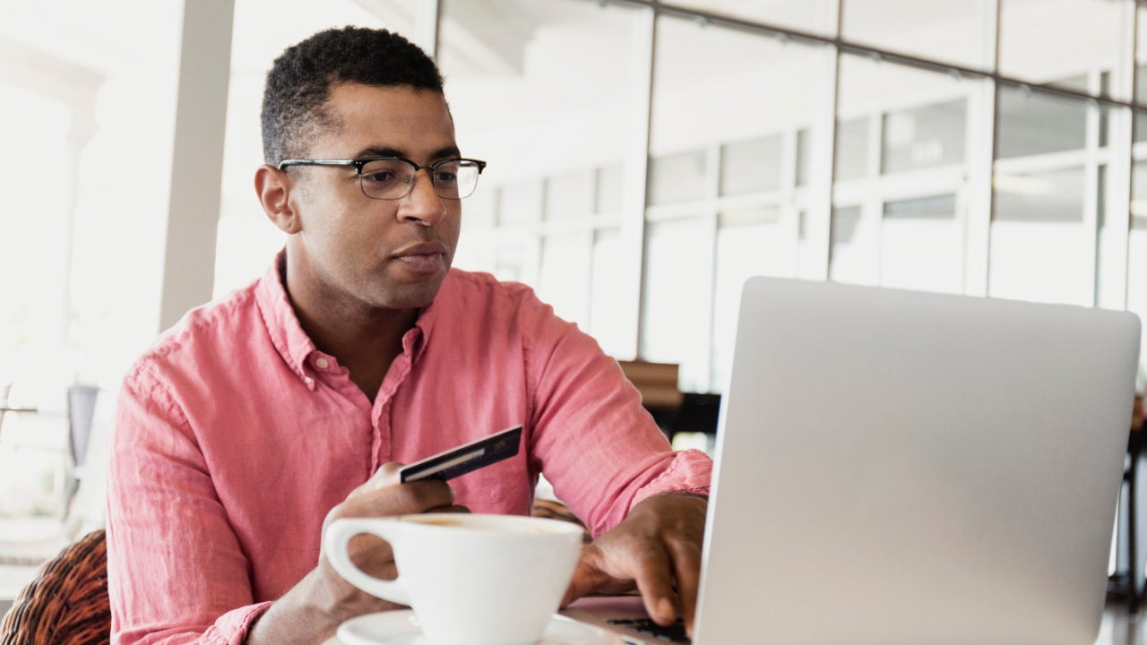Man in coffee shop using laptop with a card in his hand.