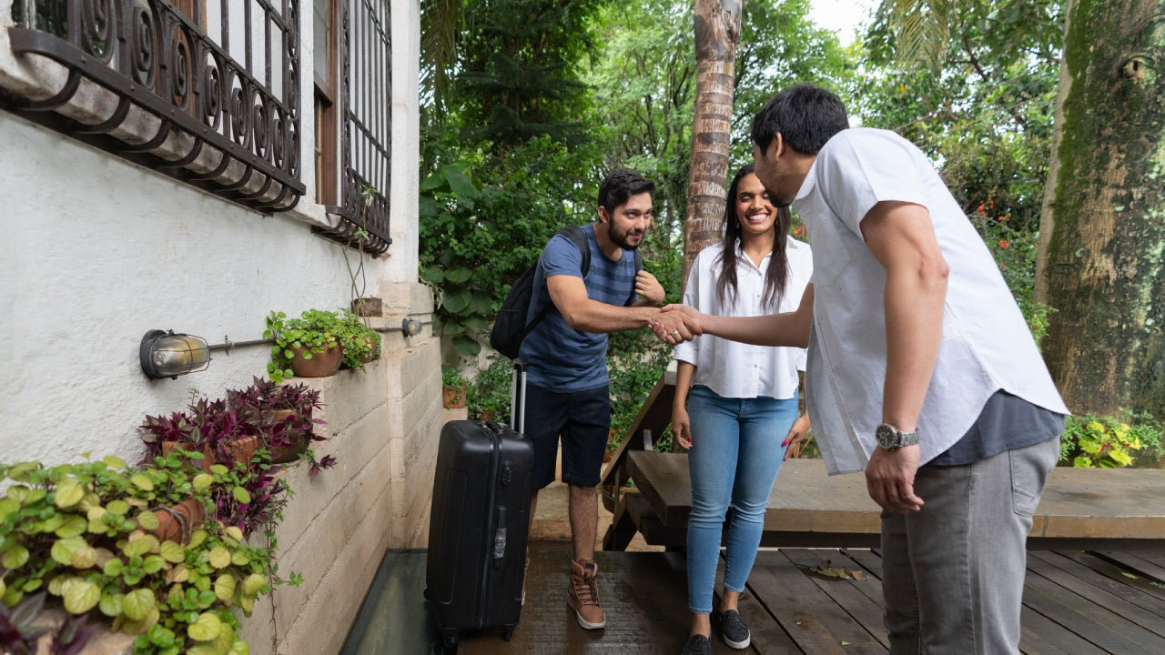 An owner of a BnB shakes hands with a younger couple that are his new tenets.
