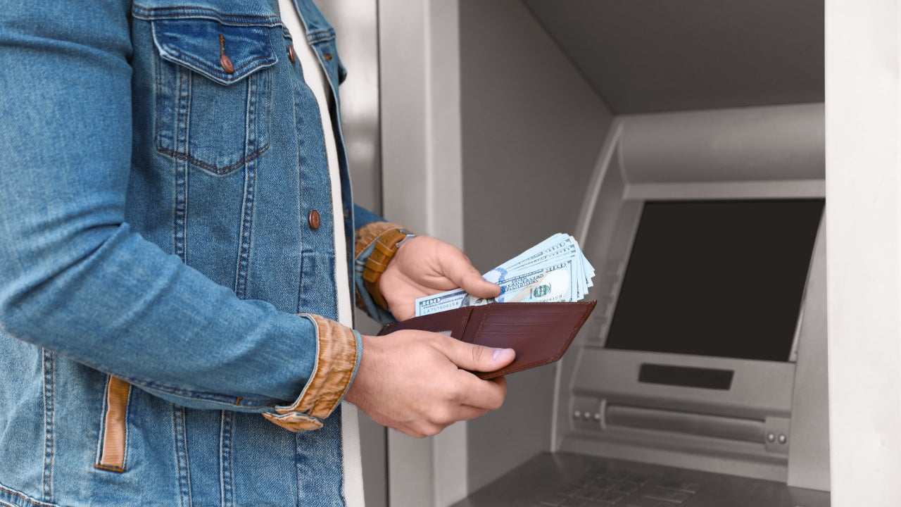 A person deposits cash at an ATM.