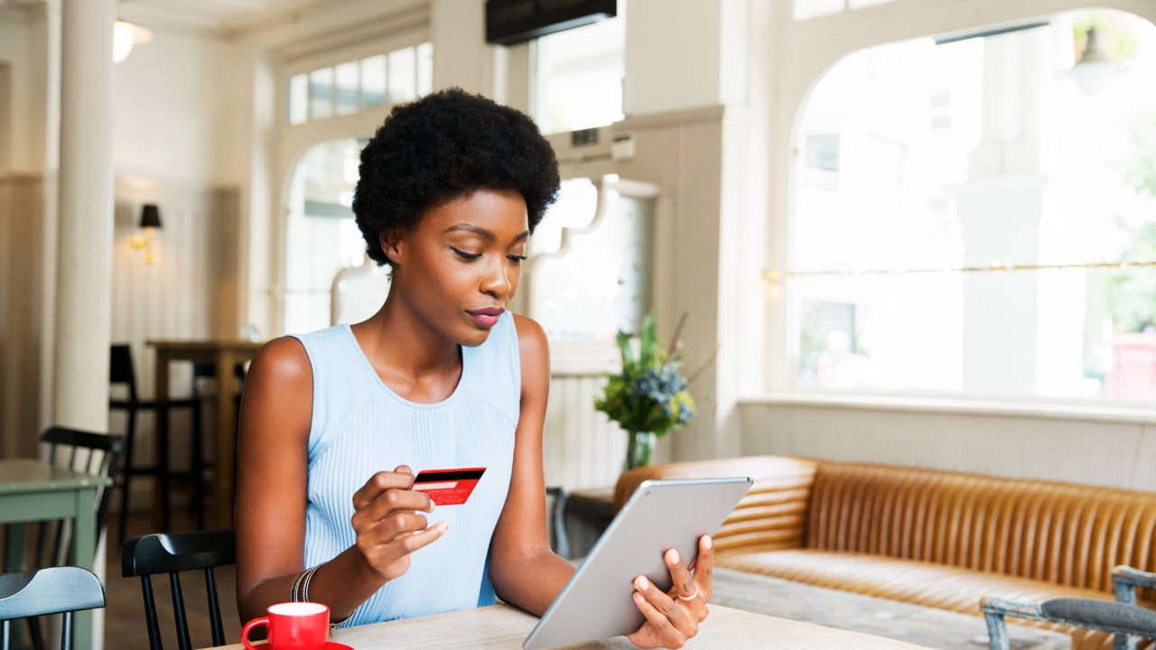 Person looking at tablet with credit card