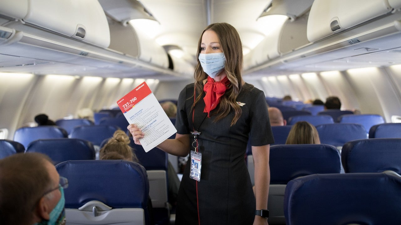 Flight attendant gives instructions wearing protective mask