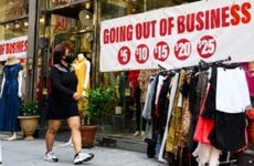 A woman walks by a store going out of business in New York City.