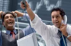 Two traders hold phones and celebrate