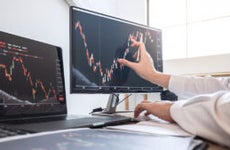 A man's hand traces a stock chart on a computer monitor