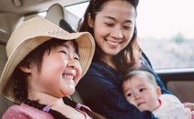 Asian woman sits in the back seat of a car with her infant child in her arms. Her daughter sits next to her, smiling and wearing a floppy straw hat.