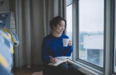 Asian student sitting by the window of her apartment looking out over the city with a pen and notepad in one hand and a cup of coffee in the other.