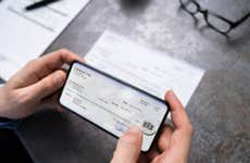 A person deposits a check with his smartphone.