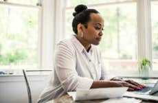 A black woman with her hair done up in a bun sitting at her desk in front of a laptop.