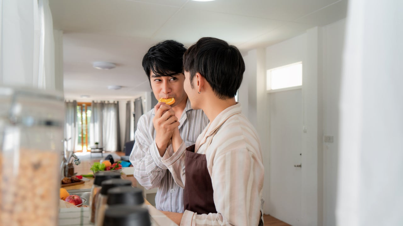 Asian gay couple chopping up fruit in the kitchen.
