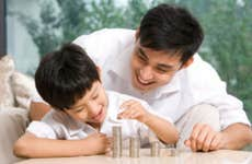 A smiling Asian father helps his son stack coins