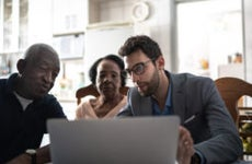 Older black couple sits with an insurance specialist in front of a laptop.