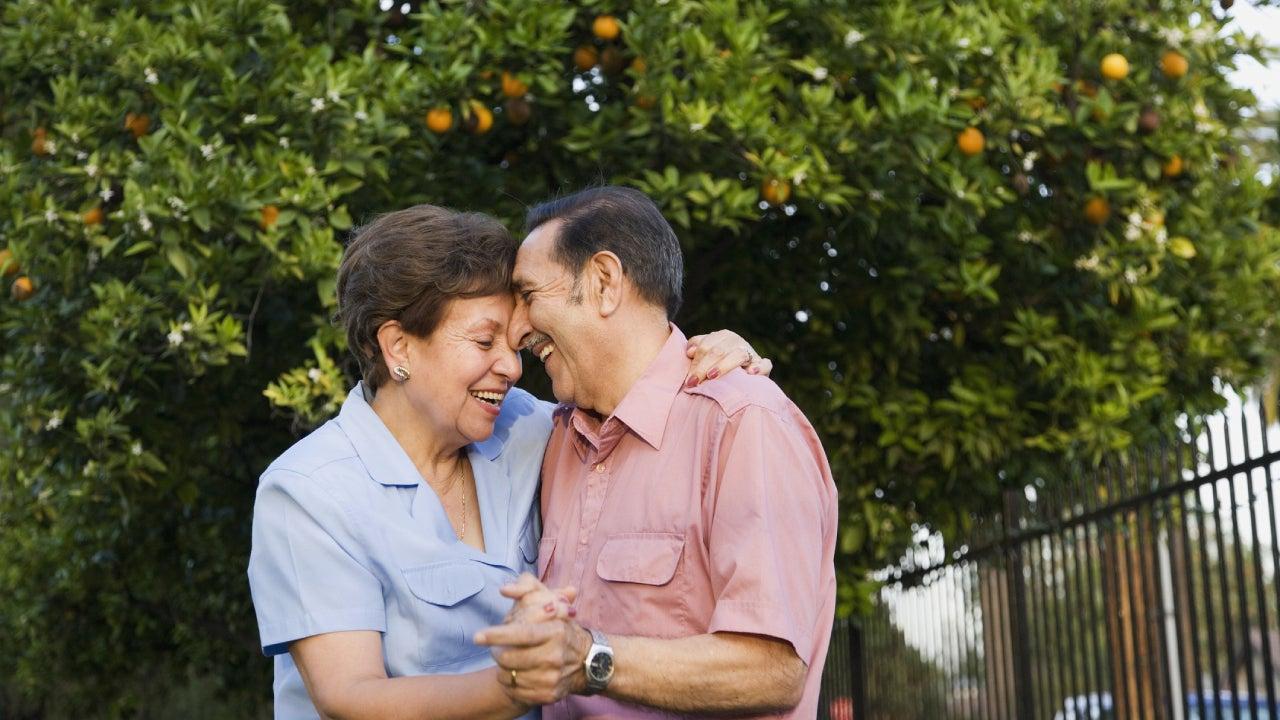 Hispanic family enjoying a dance together in an orange grove.