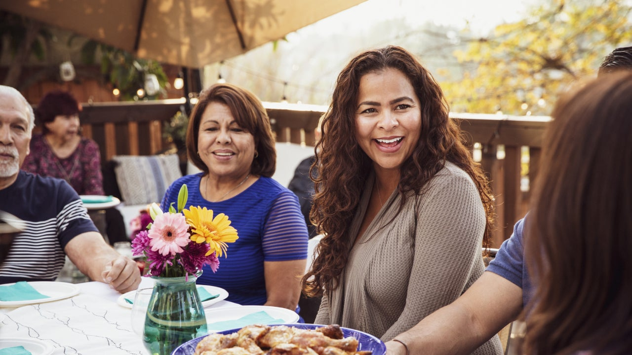 Hispanic family enjoying a nice dinner out on the porch.