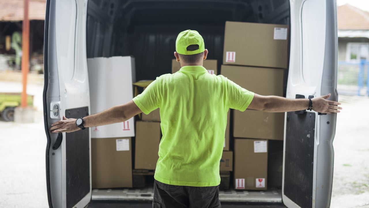 Working man in neon hat and shirt opens the rear doors to his delivery van revealing stacks of boxes for delivery.